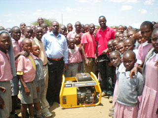 Surrounded by kids and presenting a generator to a school